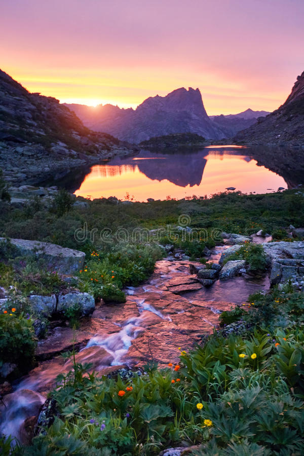 Sunset in mountains near river. Sunlight reflected on mountain tops. Golden light from sky reflected in a mountain river. Ergaki. Sunset in mountains near river royalty free stock photography