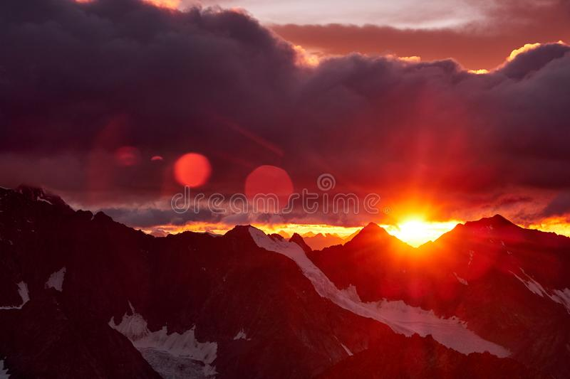 Sunset in mountains. Reflection of red sun on mountain snow peaks and clouds. Altai, Belukha area.  stock photo