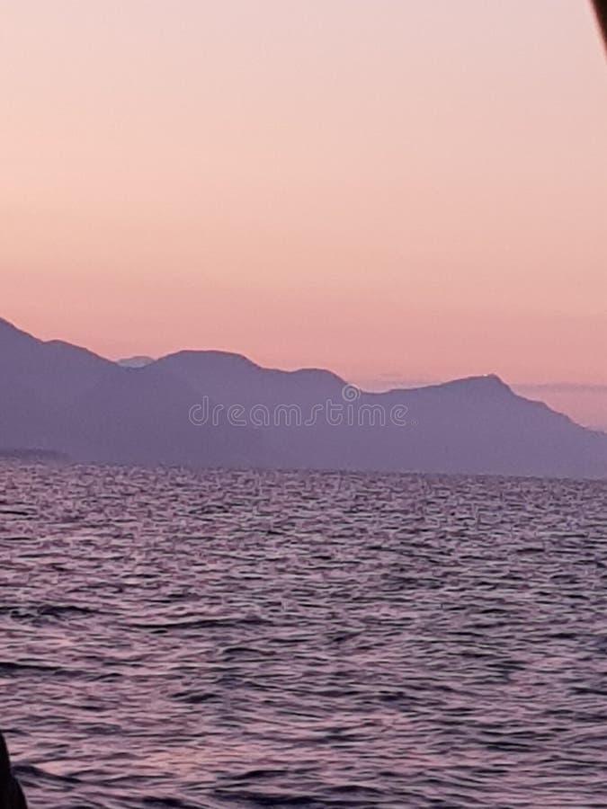 Sunset. Mountains. Sea. Pink royalty free stock image