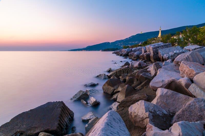 Sunset near the old lighthouse of Trieste. Sunset at the beach below the lighthouse of Trieste, Friuli Venezia-Giulia, Italy stock image