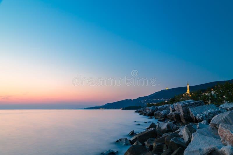 Sunset near the old lighthouse of Trieste. Sunset at the beach below the lighthouse of Trieste, Friuli Venezia-Giulia, Italy royalty free stock photo