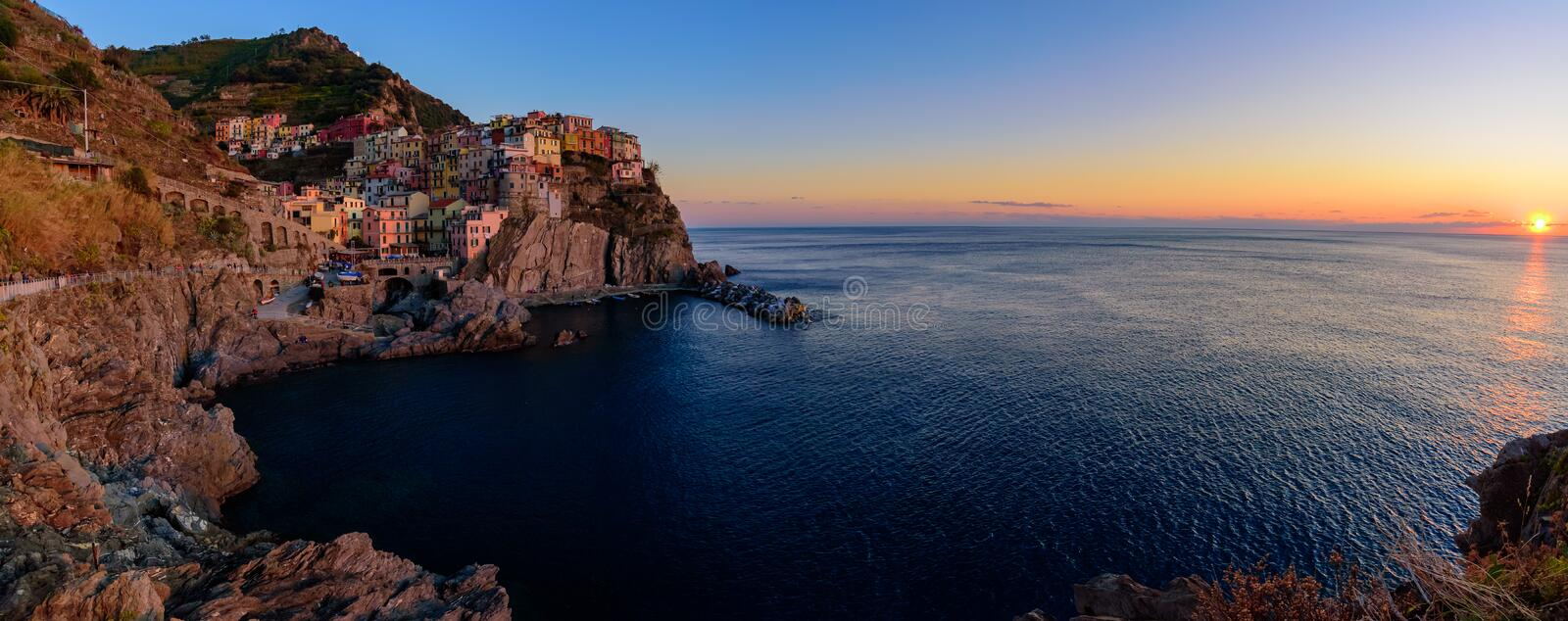 Sunset and night view of Manarola, one of the five Mediterranean villages in Cinque Terre, Italy, famous for its colorful houses stock image