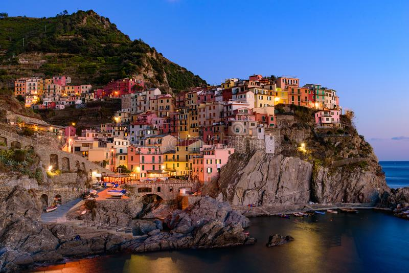 Sunset and night view of Manarola, one of the five Mediterranean villages in Cinque Terre, Italy royalty free stock photo