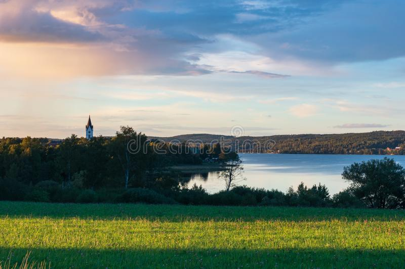 Sunset in Nora, Sweden. View over landscape in Nora town, Sweden with church tower sticking up stock image