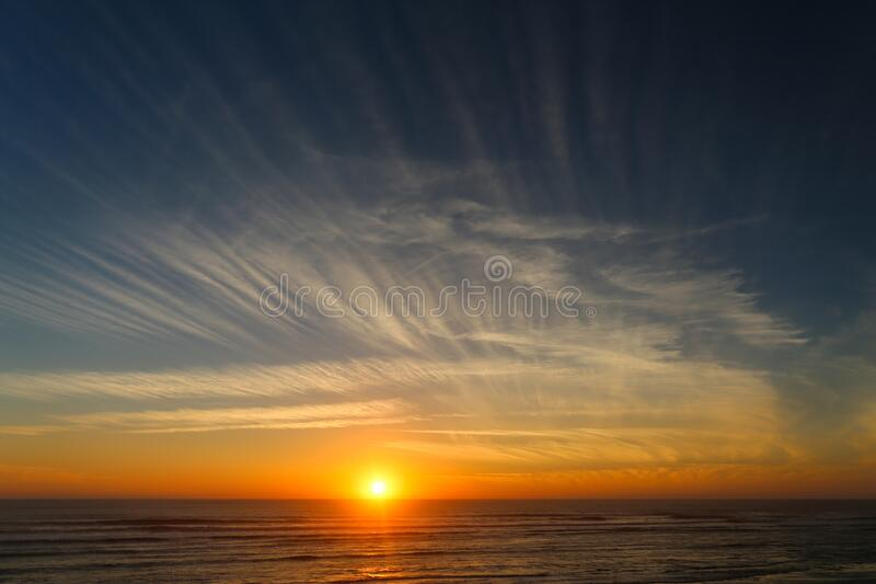 Sunset on the ocean with beautiful clouds. And waves royalty free stock photo