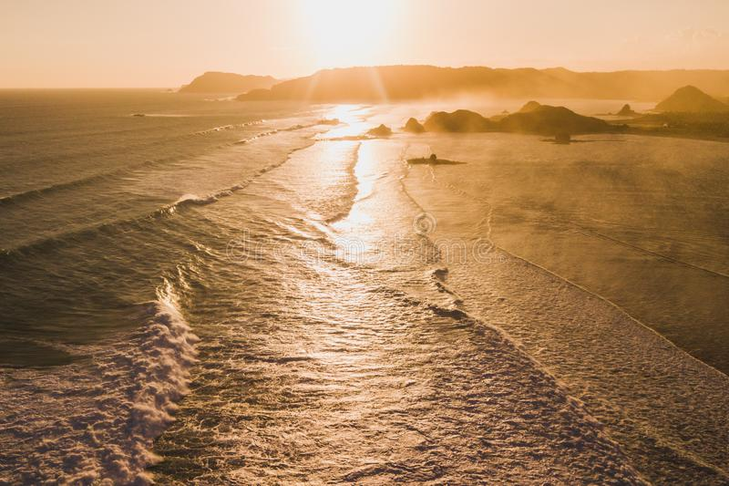 Sunset ocean landscape with waves, layered hills. Sunset landscape with huge waves and mountain hills on horizon. Golden, yellow and orange colors. Lombok royalty free stock image