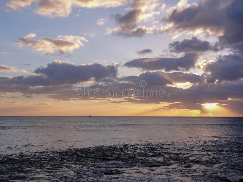 Sunset and Sailboat in Hawaii. Sunset off the coast of Oahu with a sailboat in the distance stock photography