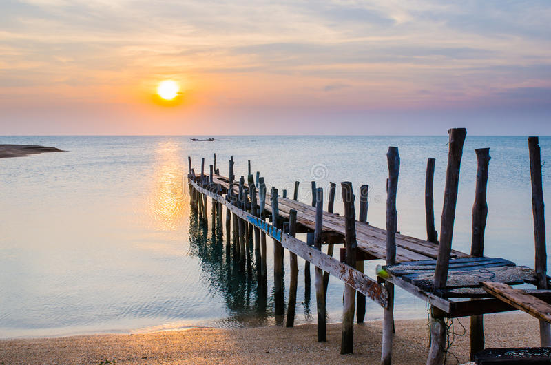 Sunset with Old ruin of pier. Old pier or a wooden bridge is broken on the beach into the sea with sunset at small island, Thailand royalty free stock photos