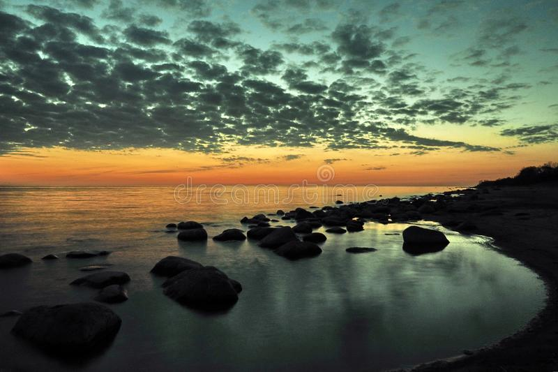 Sunset orange and blue clouds on sky over sea coast royalty free stock image