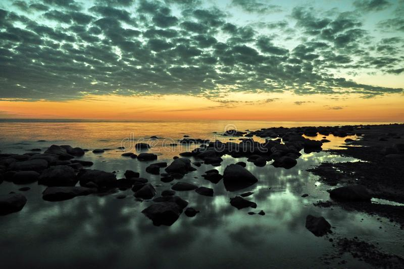 Sunset orange and blue clouds on sky over sea coast stock photos