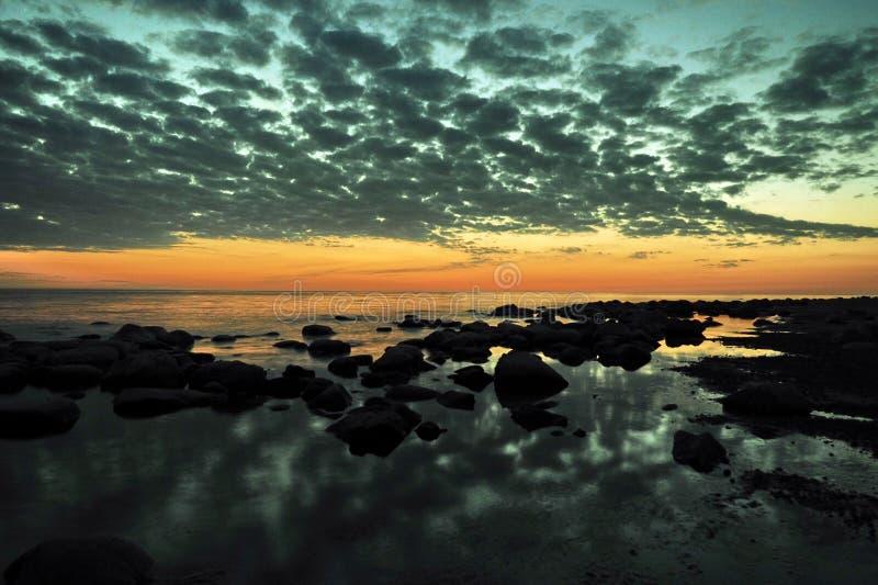 Sunset orange and blue clouds on sky over sea coast stock image