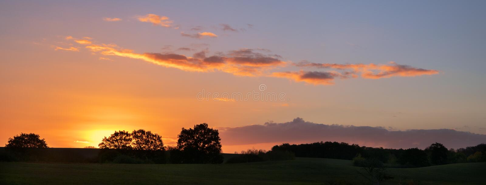 Sunset with orange clouds over a wide rural landscape with meadows and trees, panorama format with copy space stock photo