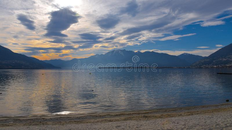 Sunset with orange-colored clouds reflecting in the lake water. In january stock photography