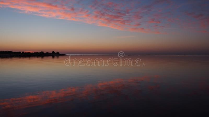 Sunset and pink clouds over river royalty free stock photography