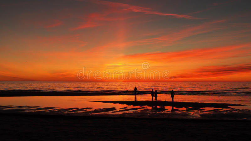 Sunset red sky and people on tehe beach stock photos