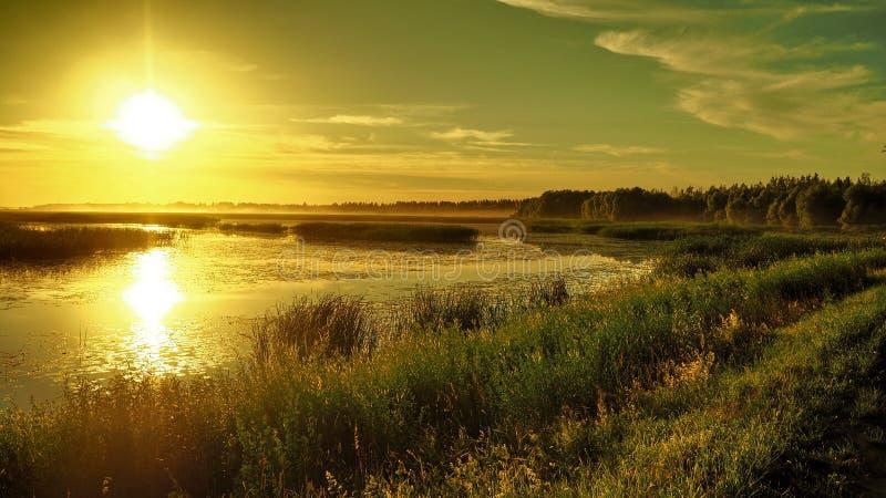 Sunset and orange sky over big lake Lubanas royalty free stock image