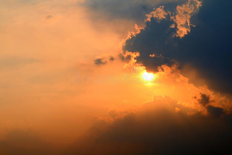 Sunset, orange sky sun sets over cloud dark, gold sky sun lighten clouds evening stock image