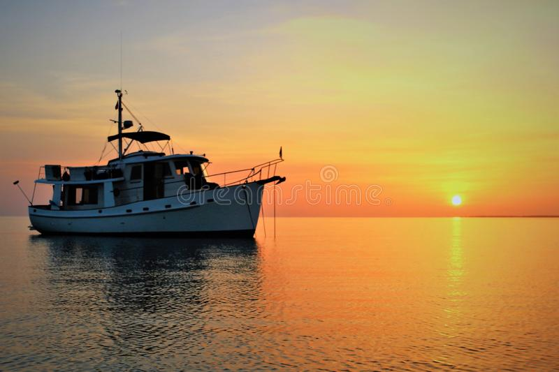 Sunset on Our Kadey Krogen 42 anchored at Annie Bight, Eleuthera Bahamas. Flat weather against an orange sky stock photography