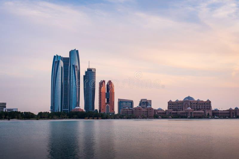 Sunset over Abu Dhabi skyline and Emirates palace. Beautiful sunset over Abu Dhabi skyline and Emirates palace royalty free stock images