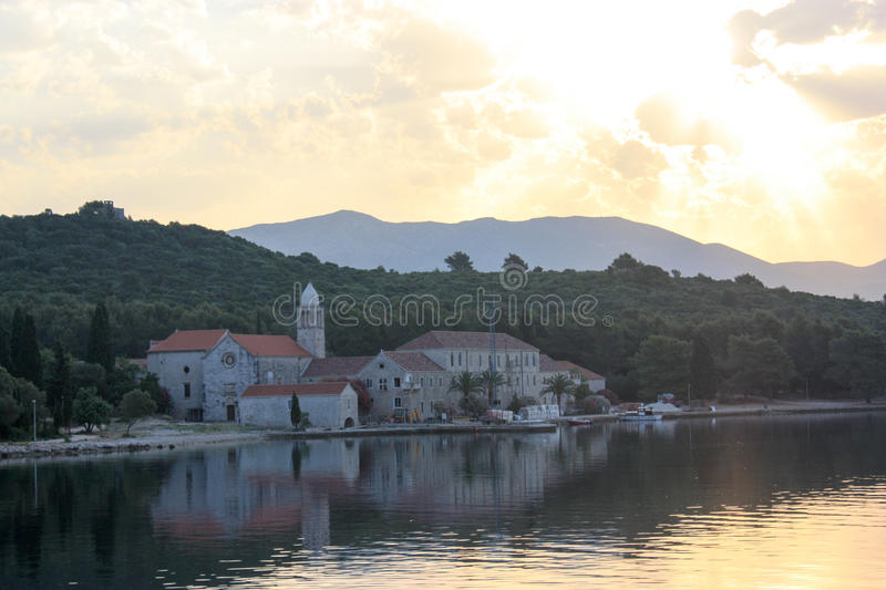 Sunset over an Adriatic island. A view of a monastery on an island near Korcula in Croatia, Still water in front of the boat looking towards the island and a big stock photo