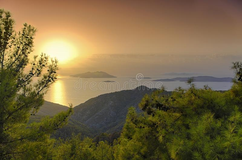 Sunset over the Aegean sea and Dodecanese Islands. Framed by fir branches stock images