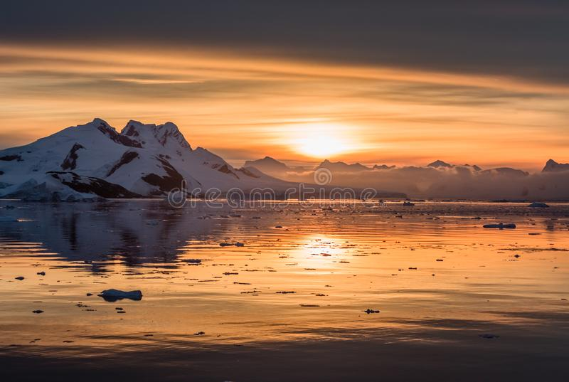 Sunset over antarctic lagoon with drifting icebergs and snow peaks in the background, Lemaire Channel stock photography