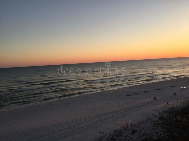 Sunset over the Atlantic Ocean with waves slowly washing ashore on a sandy beach royalty free stock photo