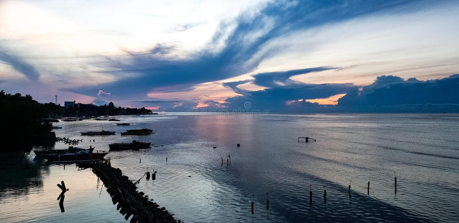 Sunset over the bay at Oslob, Visayas, Philippines. A lovely cool sunset over the bay at Oslob, Visayas, Philippines, a popular tourist destination to go to swim stock photos