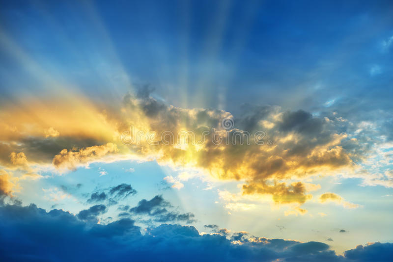 Sunset over beautiful blue sky. With sun shining through clouds stock image