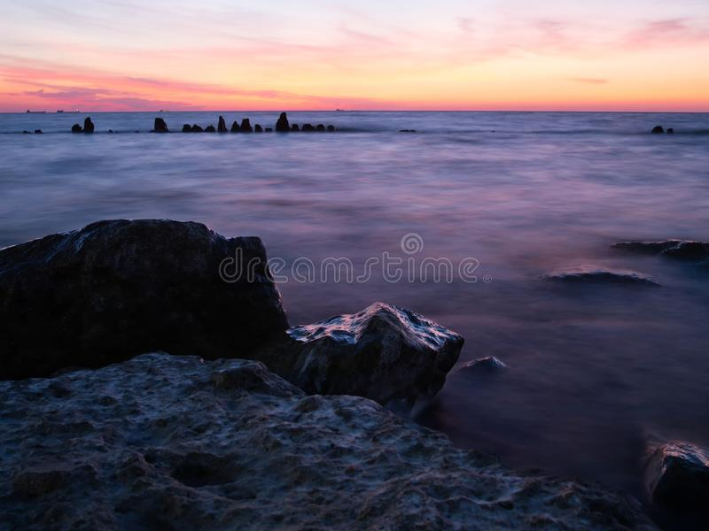 Sunset over blurred waterfront. Log exposure waterfront seascape at sunset with wooden pier poles stock photo
