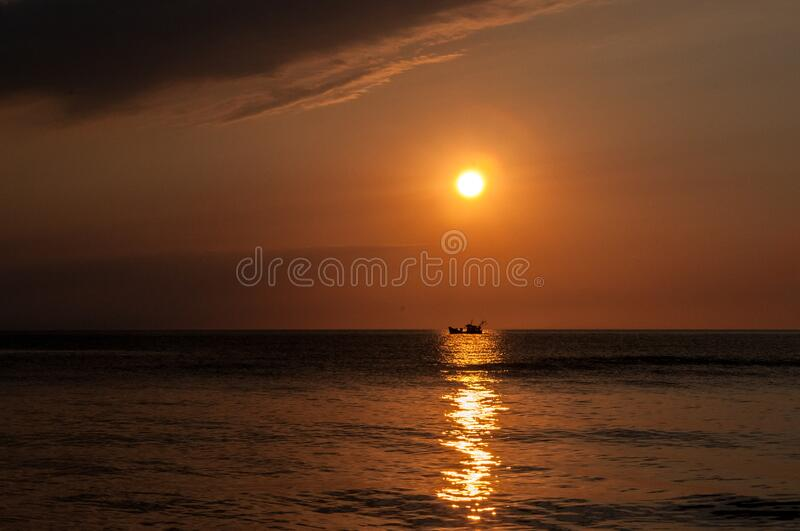 Sunset over boat on water royalty free stock photos