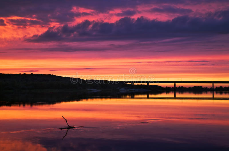 Sunset over the bridge, purple blue yellow orange sky, orange clouds. Stick in the water, bush in water stock photos