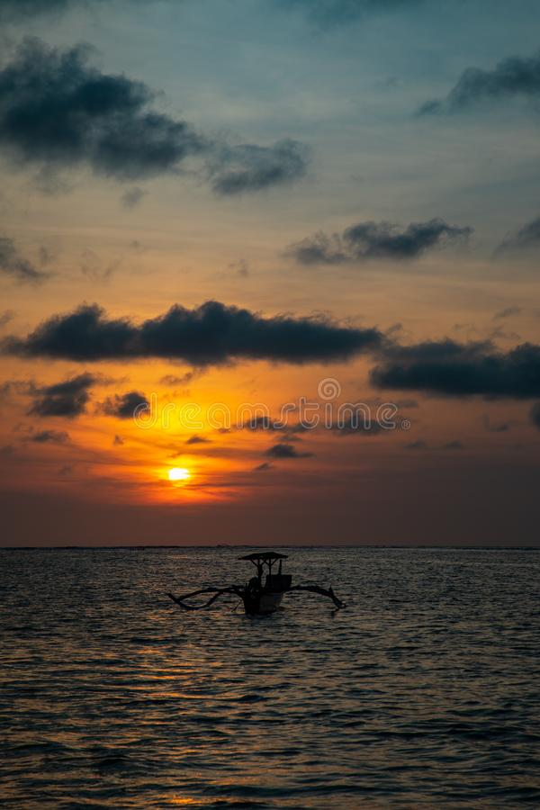 Sunset over calm ocean with balinese boat stock image
