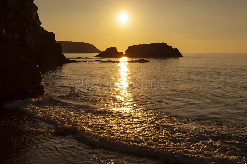 Sunset at Tresaith Beach. Sunset over Cardigan bay viewed from Tresaith, Ceredigion. Looking towards the headland of Aberpoth royalty free stock photography