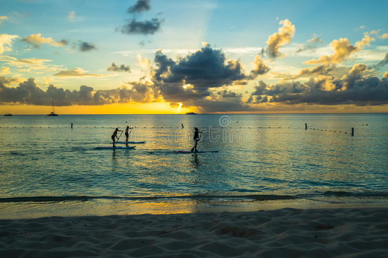Sunset over a caribbean beach with standup paddle boarders. Sunset over a caribbean beach with golden sand in the foreground with standup paddle boarders stock images