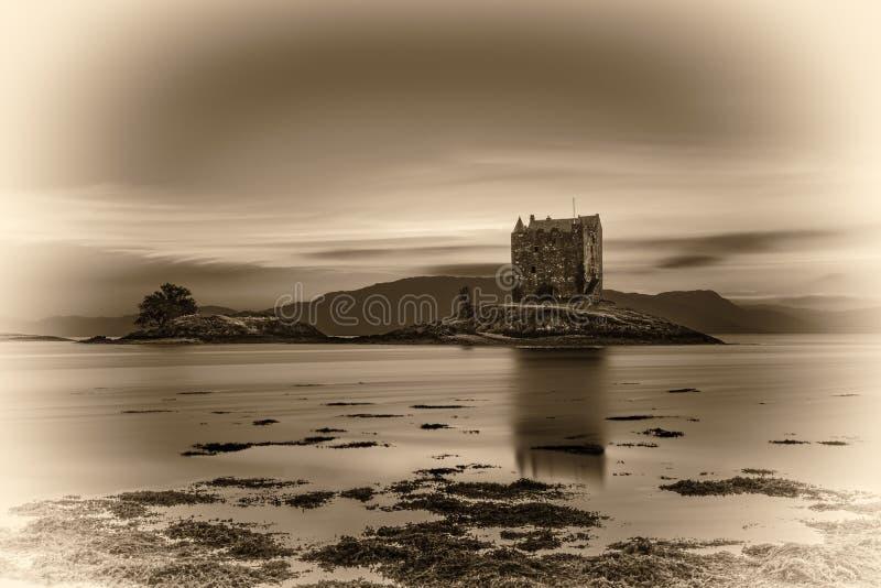 Sunset over Castle Stalker, Scotland, United Kingdom. Sunset over Castle Stalker, Highlands, Scotland, United Kingdom. Vintage black and white processed stock image