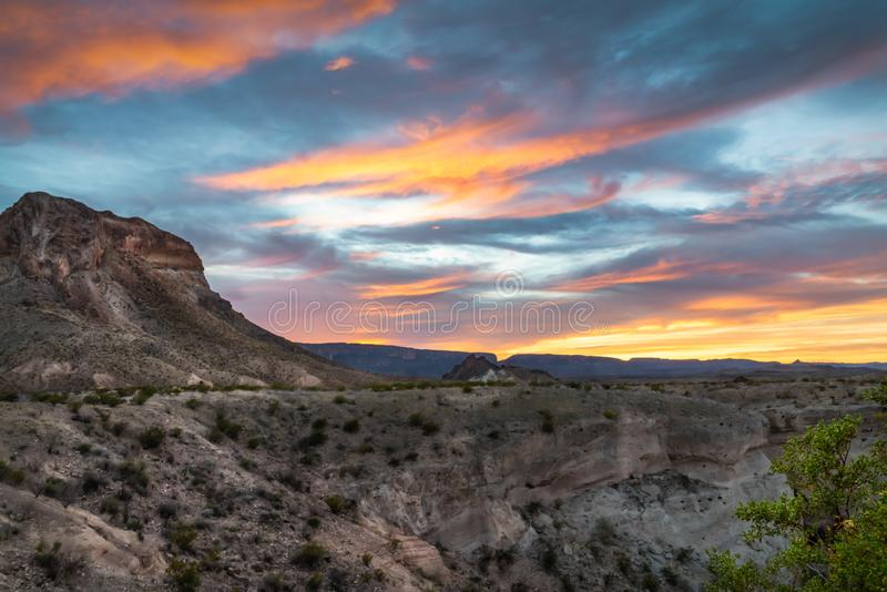 Sunset over Cerro Castellan butte in Big Bend National Park. With streaks of yellow, orange and pink against a blue sky stock photos