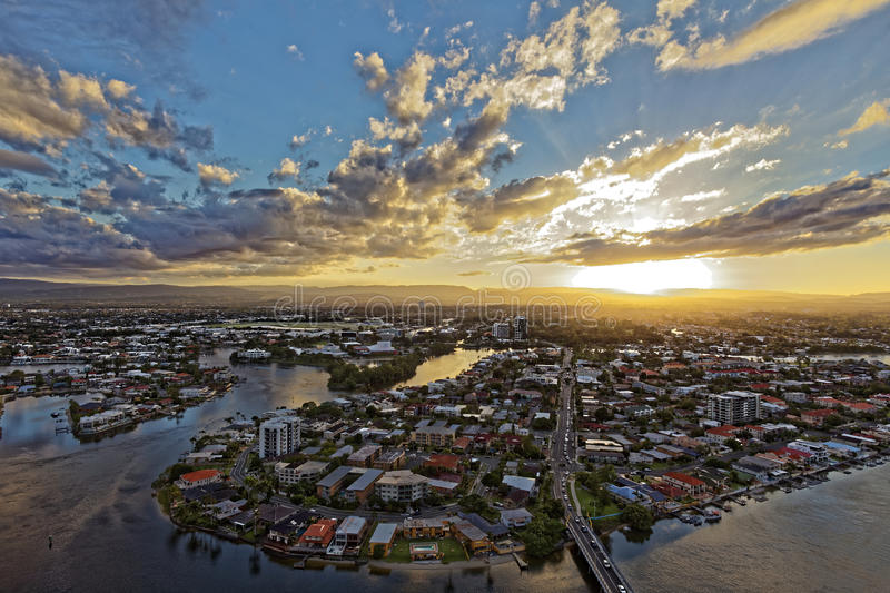 Sunset over city at river by intermittent clouds aerial view. Aerial image of Nerang river and a district of Surfers Paradise, Gold Coast, Australia, with view royalty free stock photos