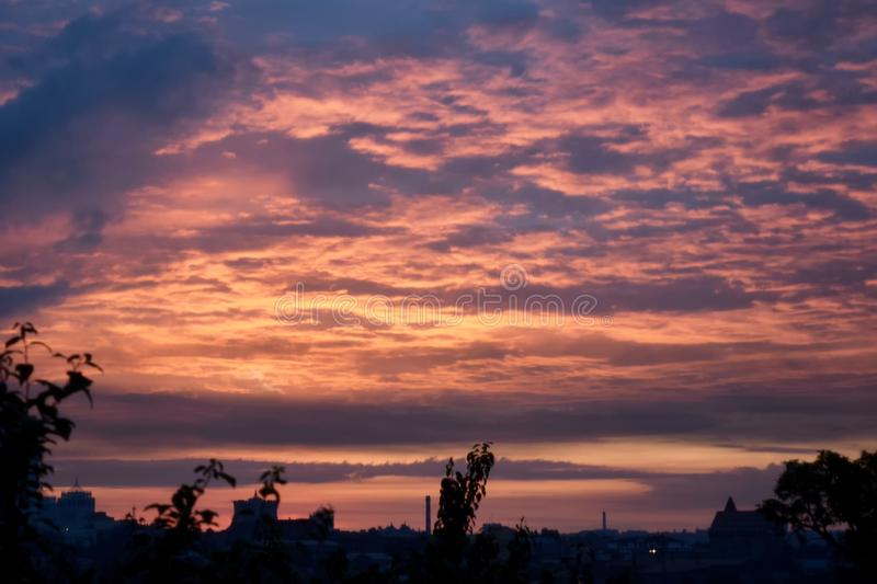 Sunset over city, round red sun and the night stock photography