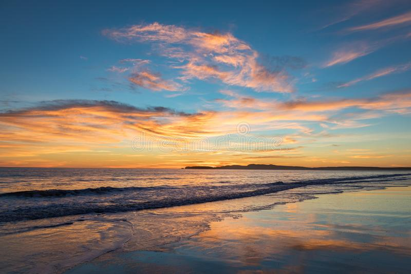 Sunset over coast with saturated colors in the sky and reflections in the water. Saturated and vibrant sky with clouds at sunset. Reflections in ocean waves royalty free stock photography