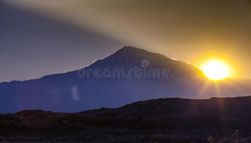 Sunset over color mountain silhouette with rays stock photo