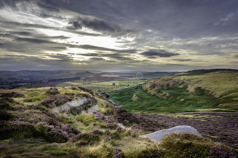 Sunset over colourful moorland in Peak District National Park, Derbyshire, Uk. Sunset  over colourful moorland and moody sky above scenic valley with hills and royalty free stock photo