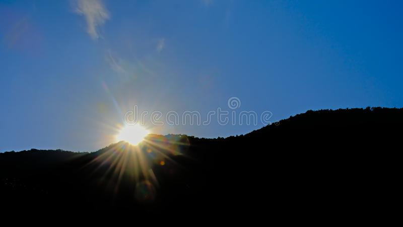 Sunset over mountain black silhouettes on a clear blue sky royalty free stock photos