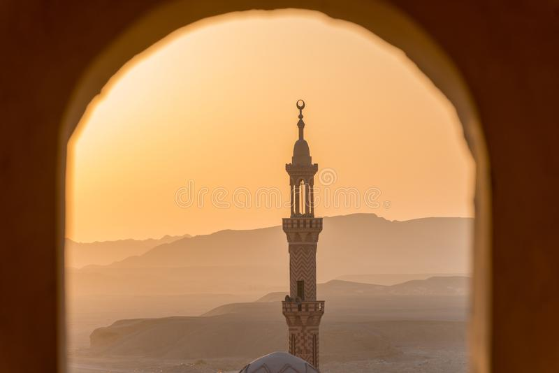 Sunset over desert with muslim mosque in the foreground. Focus on distant mountains royalty free stock images