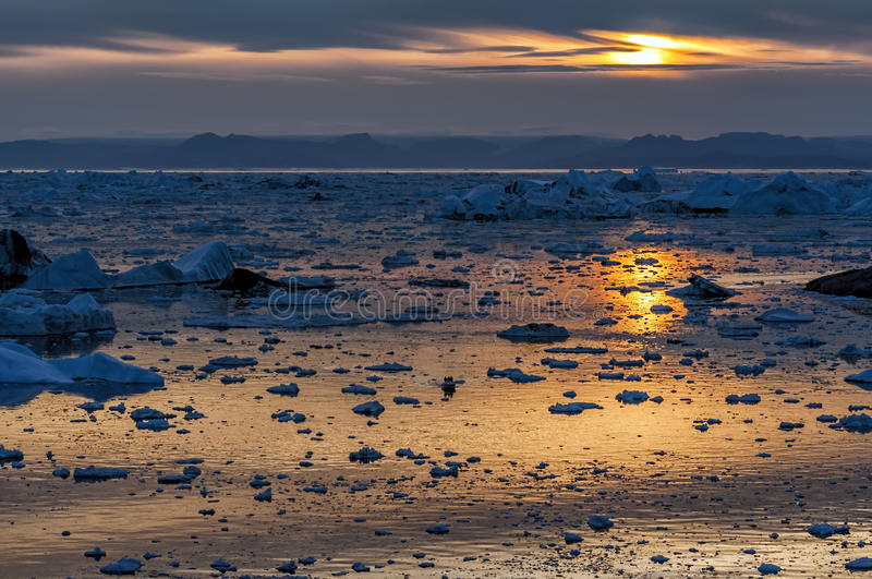 Sunset over Disko bay, Greenland. Disko Bay is a bay on the western coast of Greenland. The bay constitutes a wide southeastern inlet of Baffin Bay royalty free stock photo