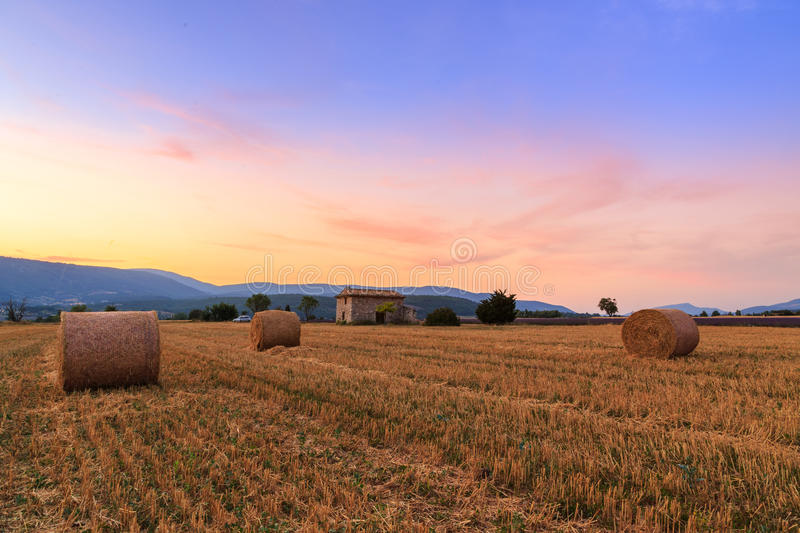 Sunset over farm field with hay bales near Sault. Provence-France stock photo