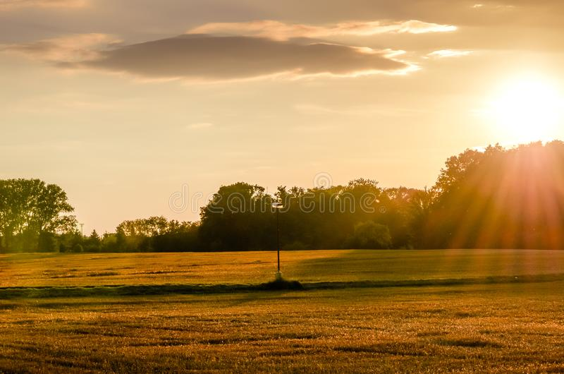 Sunset over a field path with a lamp. stock image