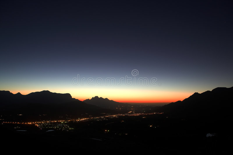 Sunset over Franschhoek. Sunset over the small town of Franschhoek and nearby wine farms. Feint star trails in the sky right after sunset stock photo