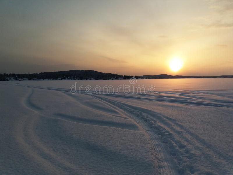 Sunset over the frozen lake in winter royalty free stock photography