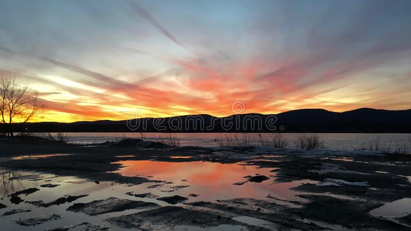 Sunset over Frozen Pontoosuc Lake at Pittsfield, MA. Pontoosuc Lake has 480 acre with a maximum depth of 35 feet and an average depth of 14 feet royalty free stock photography